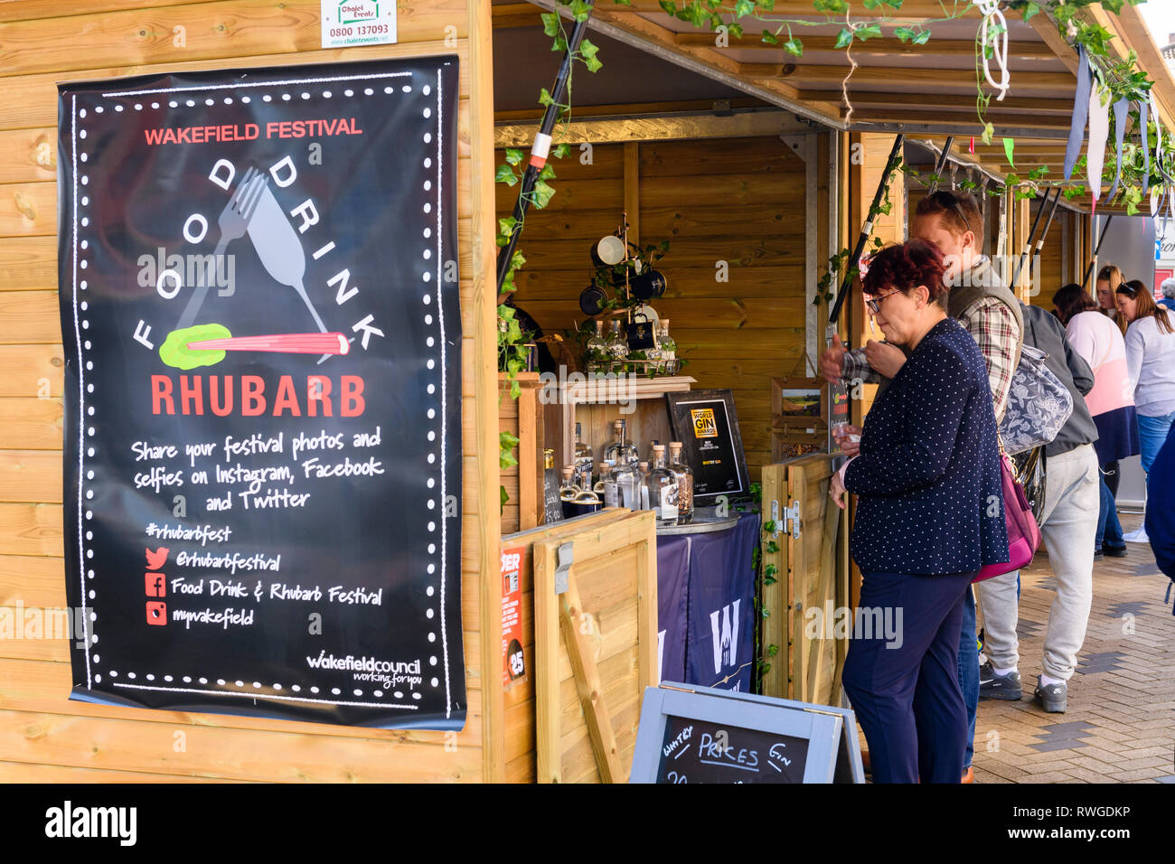 People shopping a occupato Wakefield cibo, drink & Rabarbaro Festival 2019 Visita il commercio di mercato bancarella vendendo bottiglie di gin - West Yorkshire, Inghilterra, Regno Unito Foto Stock