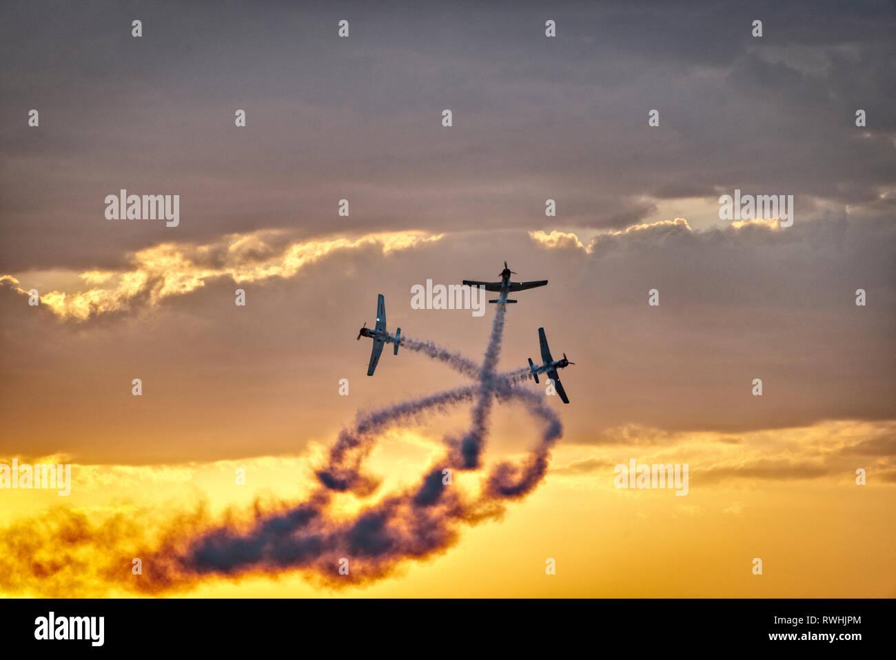 Tre aerei acrobatici attraversando nel cielo contro le nuvole e un cielo arancione Immagini Stock