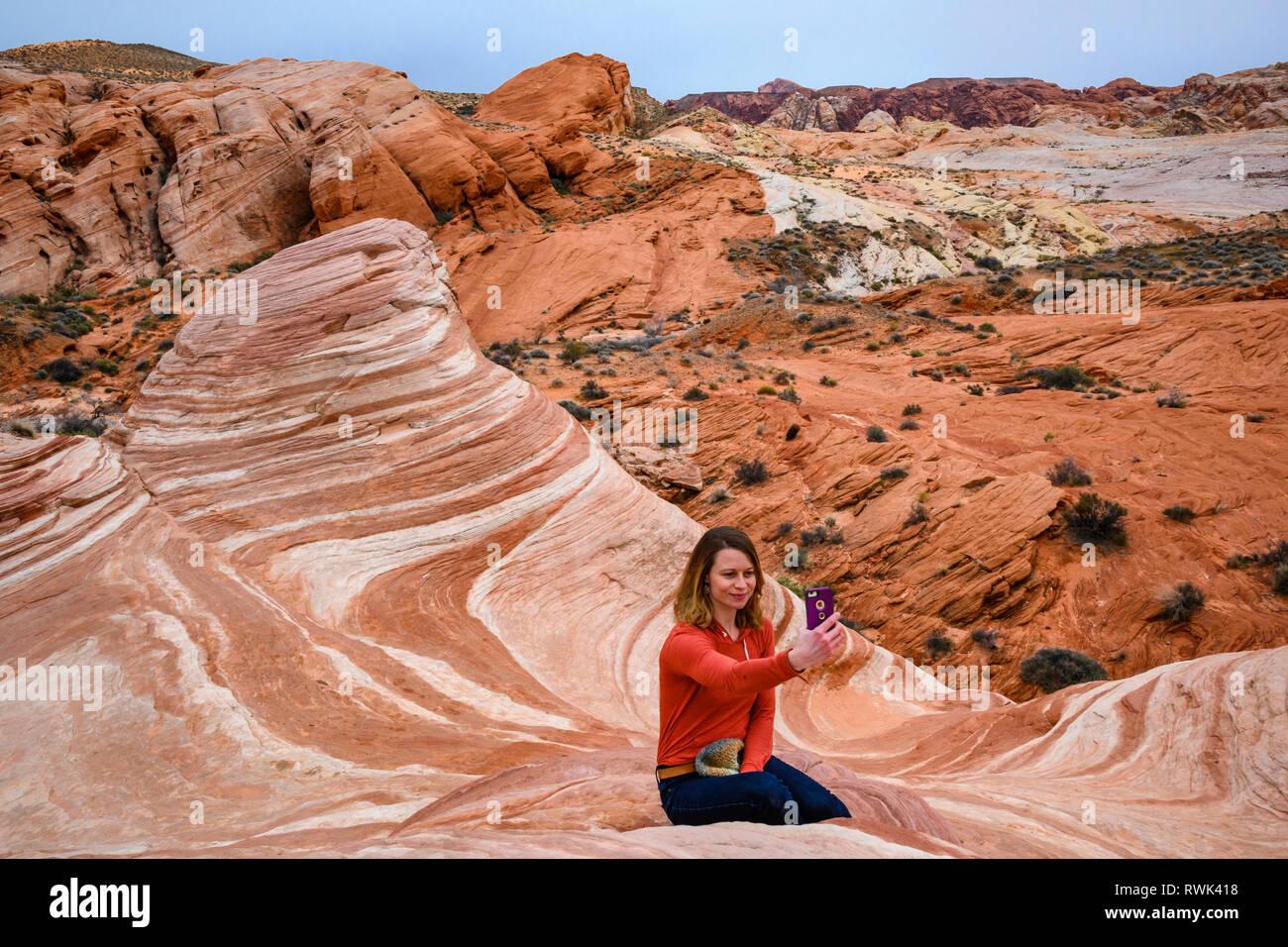 Donna prendendo selfie foto a fuoco arenaria wave rock formazione della Valle di Fire State Park, Nevada. Foto Stock