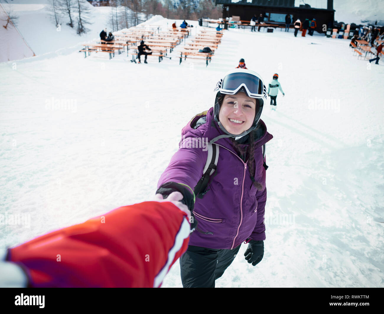 Sci giovane indossando il casco e occhiali da sci tenendo le mani sulle piste da sci Alpe Ciamporino, Piemonte, Italia Immagini Stock
