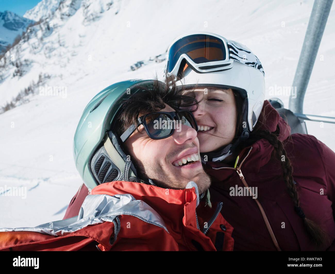 Sci giovane indossando il casco e occhiali da sci su ski lift, Alpe Ciamporino, Piemonte, Italia Immagini Stock