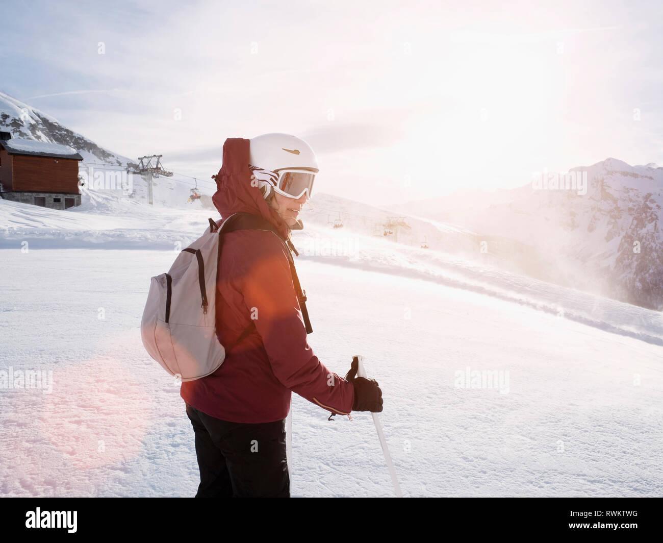 Donna giovane sciatore indossando il casco e occhiali da sci in paesaggi innevati, Alpe Ciamporino, Piemonte, Italia Immagini Stock