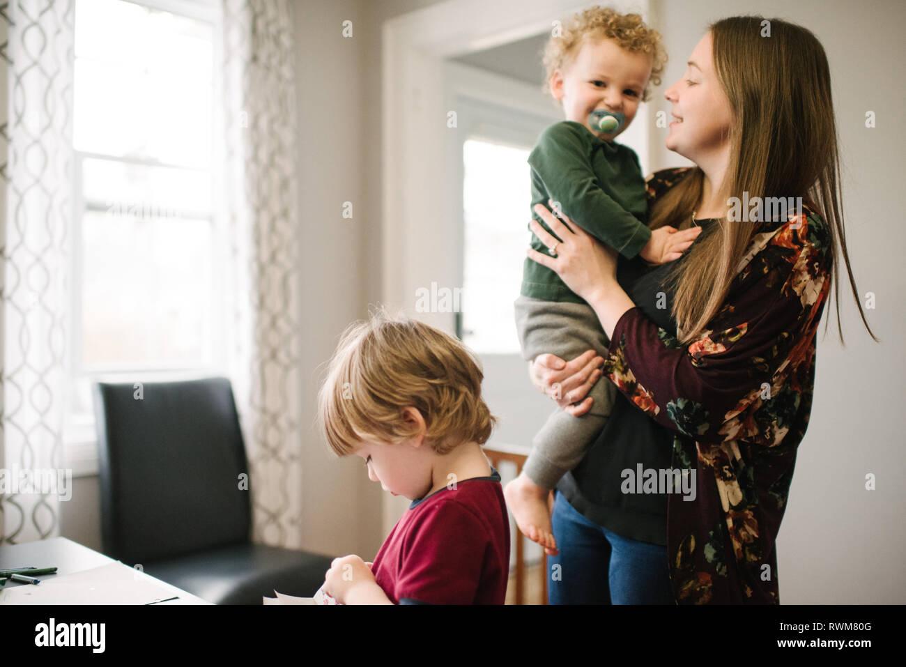 Ragazzo giocando al tavolo, madre accanto a lui Foto Stock