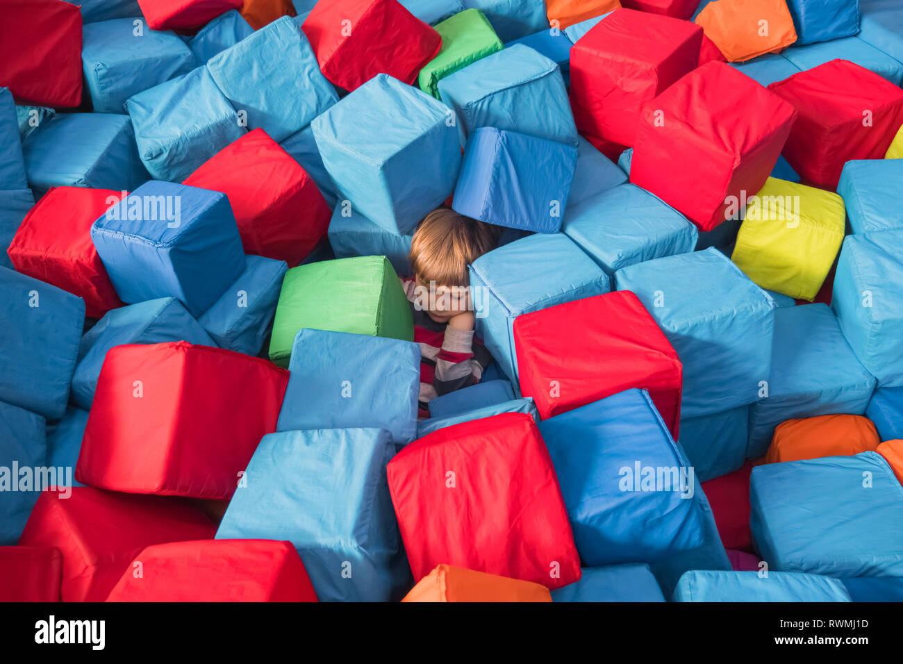 L'autismo infantile psicologia infantile concettuale. Ragazzo coperto con colorati blocchi morbidi, cubetti. Per i bambini e fisiologici per la salute psicologica Immagini Stock