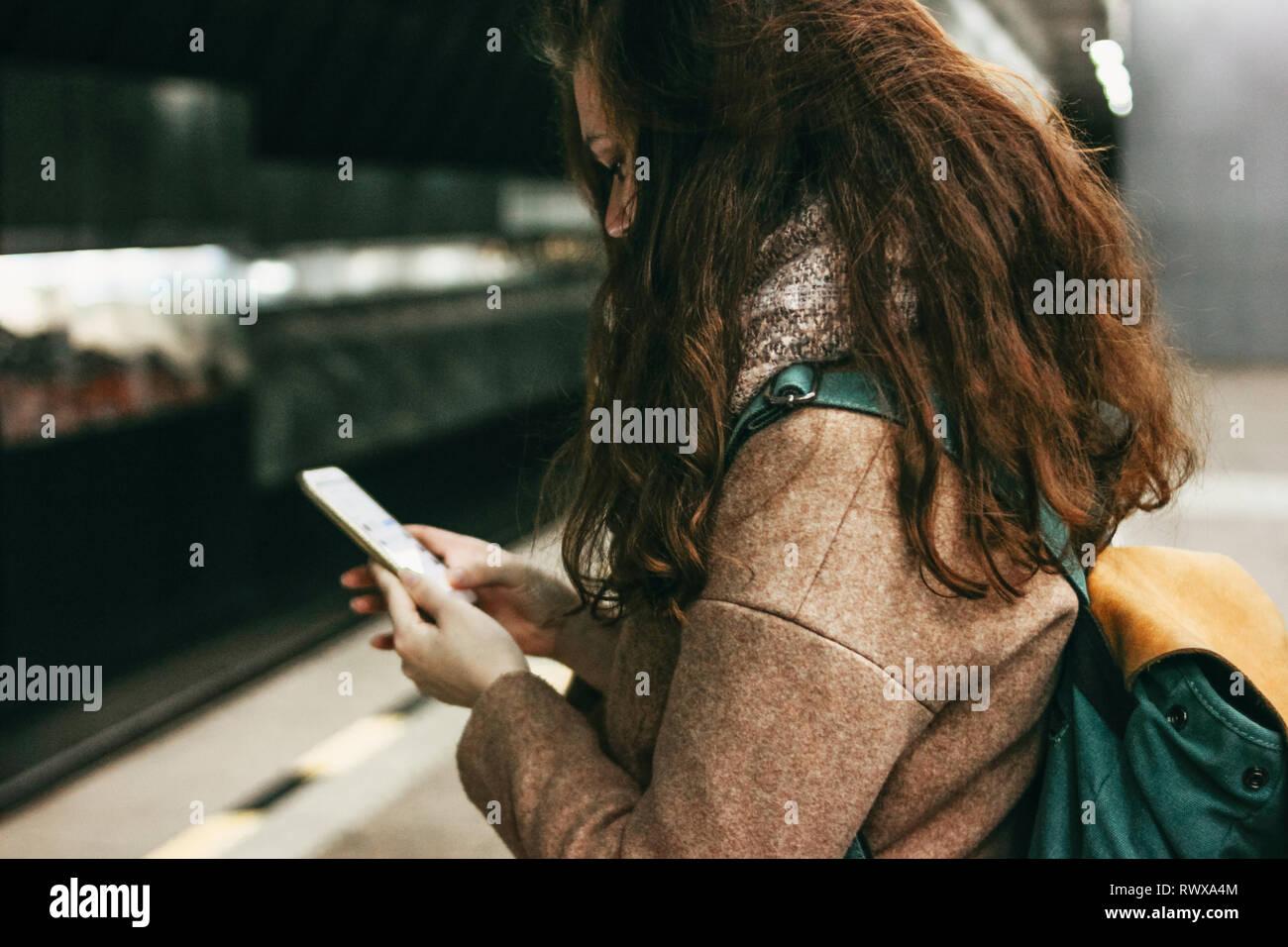 Giovane donna ricci testa rossa ragazza viaggiatori con zaino utilizzando mobile in metropolitana Foto Stock
