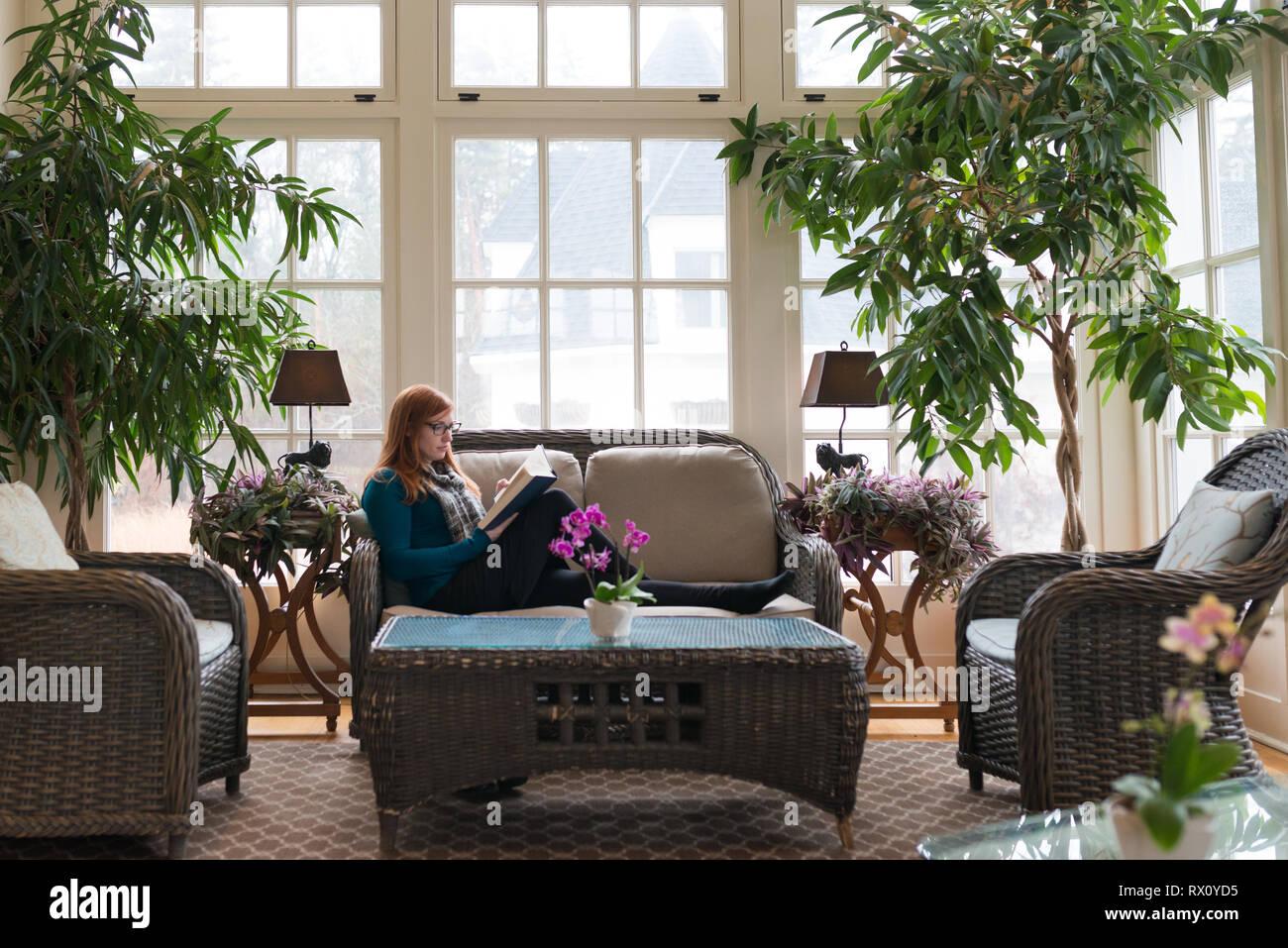 Femmina attraente utilizza il tempo libero e il grande interior design per la lettura di apprendimento auto-miglioramento Immagini Stock