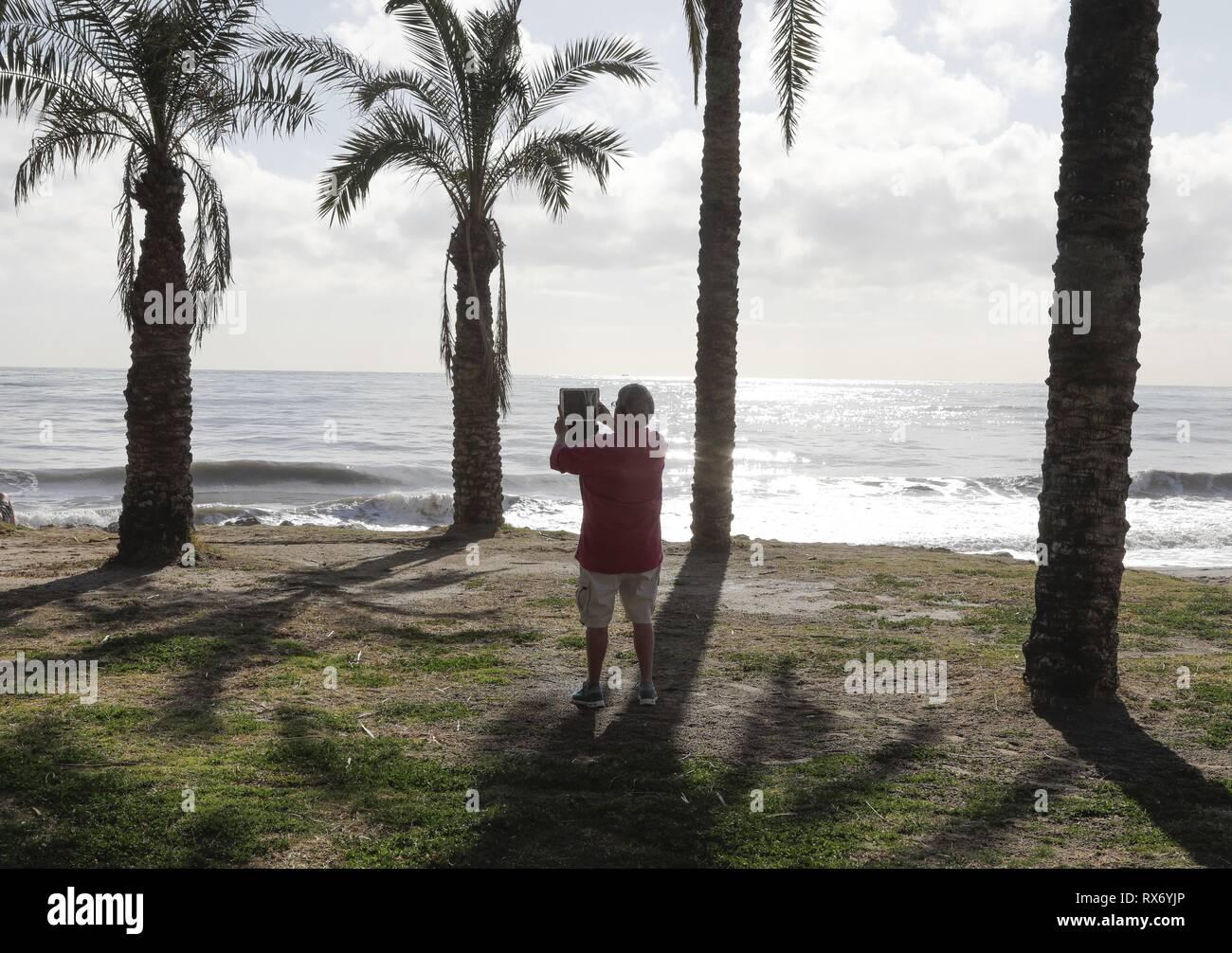 Un uomo che usa il suo tablet per fare un film presso la spiaggia di Torremolinos, Spagna, 13. Febbraio 2019. L'economia spagnola è in attesa di vedere come il futuro della Gran Bretagna la partenza dall'Unione europea potrebbe applicare in Spagna.   Utilizzo di tutto il mondo Immagini Stock