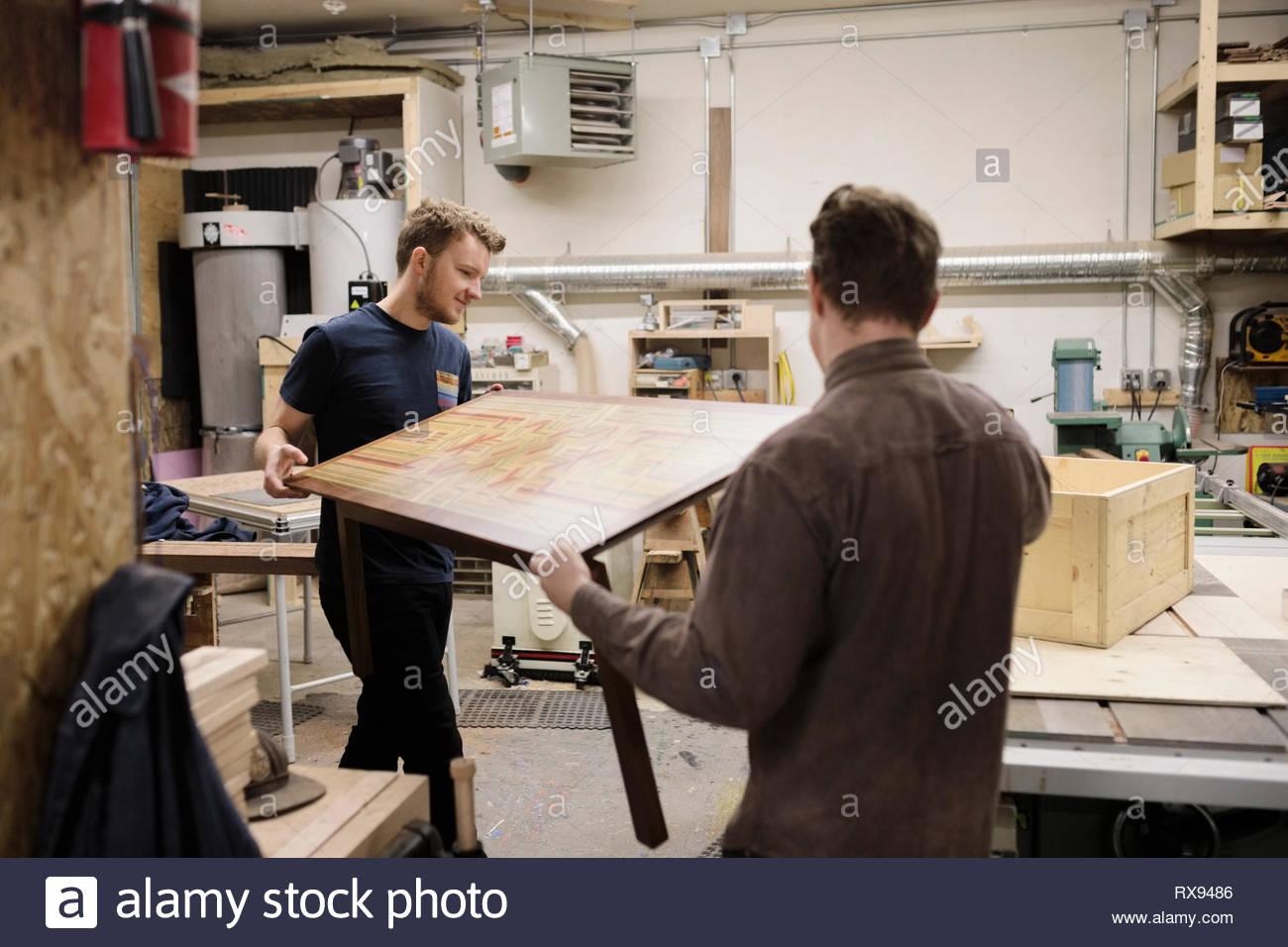 Falegnami maschio tavola portante in officina Immagini Stock
