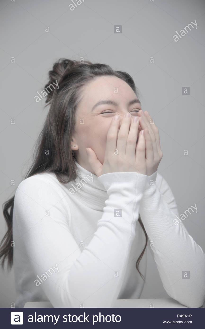 Ritratto giocoso bella giovane donna ridere con testa in mani Immagini Stock