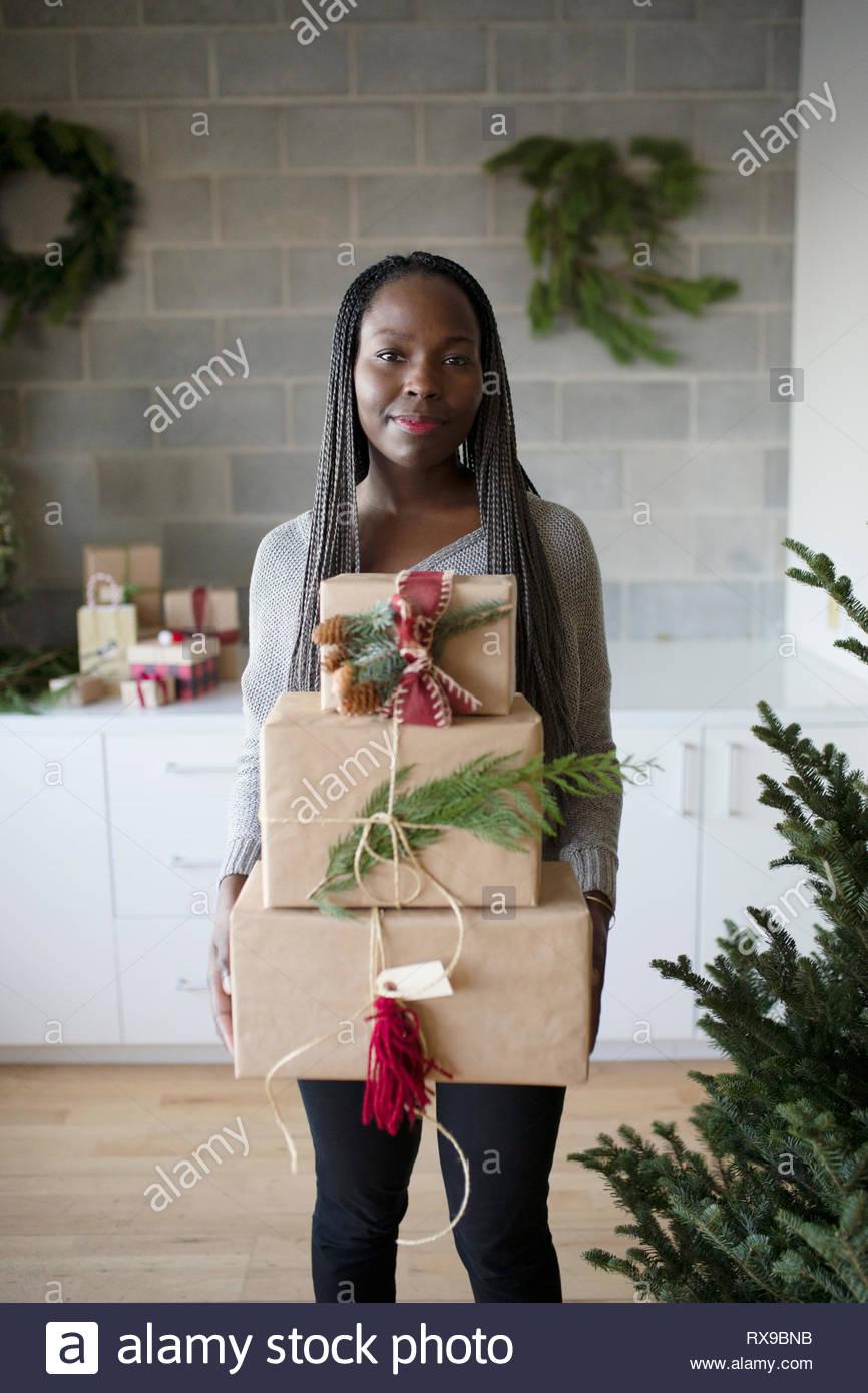 Ritratto sorridente giovane donna che porta pila di regali di natale Immagini Stock
