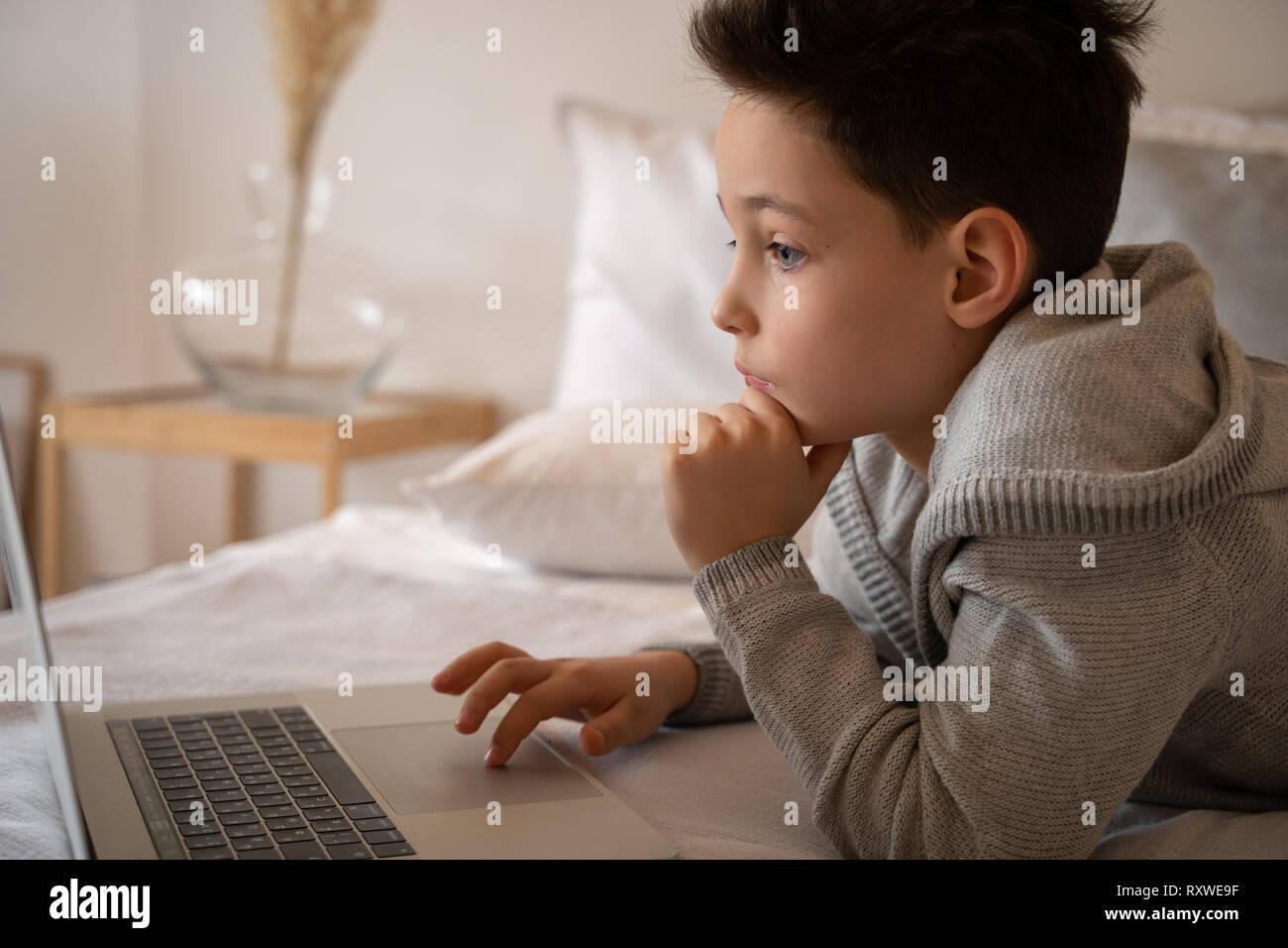 Un piccolo ragazzo seduto su un letto grande con un laptop libro e guarda nella telecamera. Immagini Stock