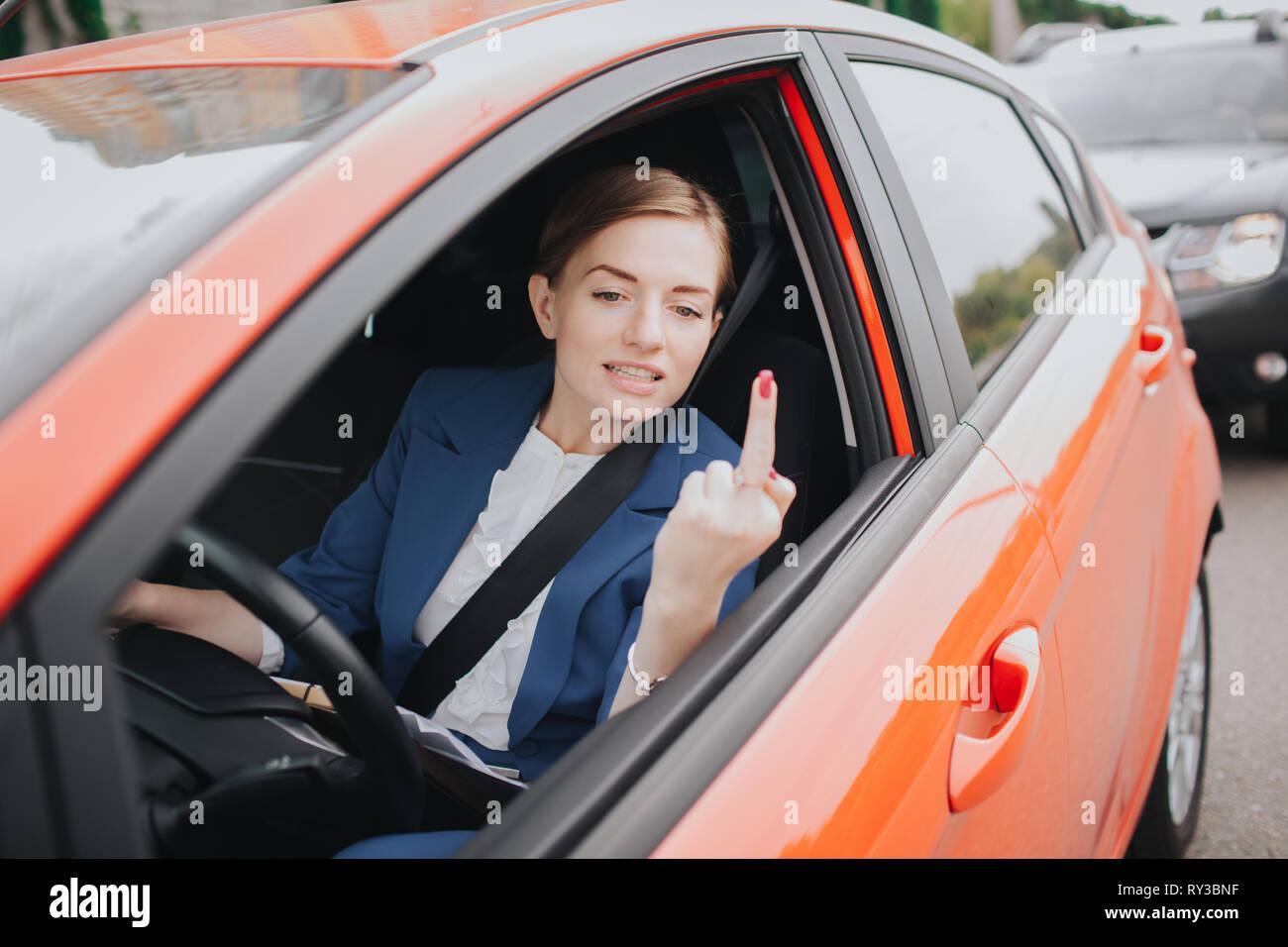 Una donna si sente lo stress sulla strada. Mostra il fatto nella finestra . Grande traffico. Business donna è in ritardo per il lavoro Immagini Stock