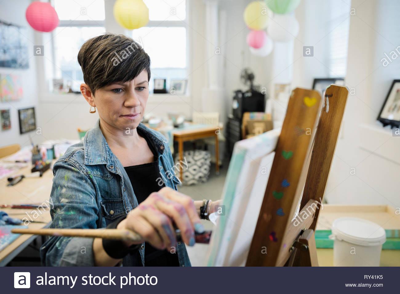 Focalizzato artista femminile pittura in studio Immagini Stock