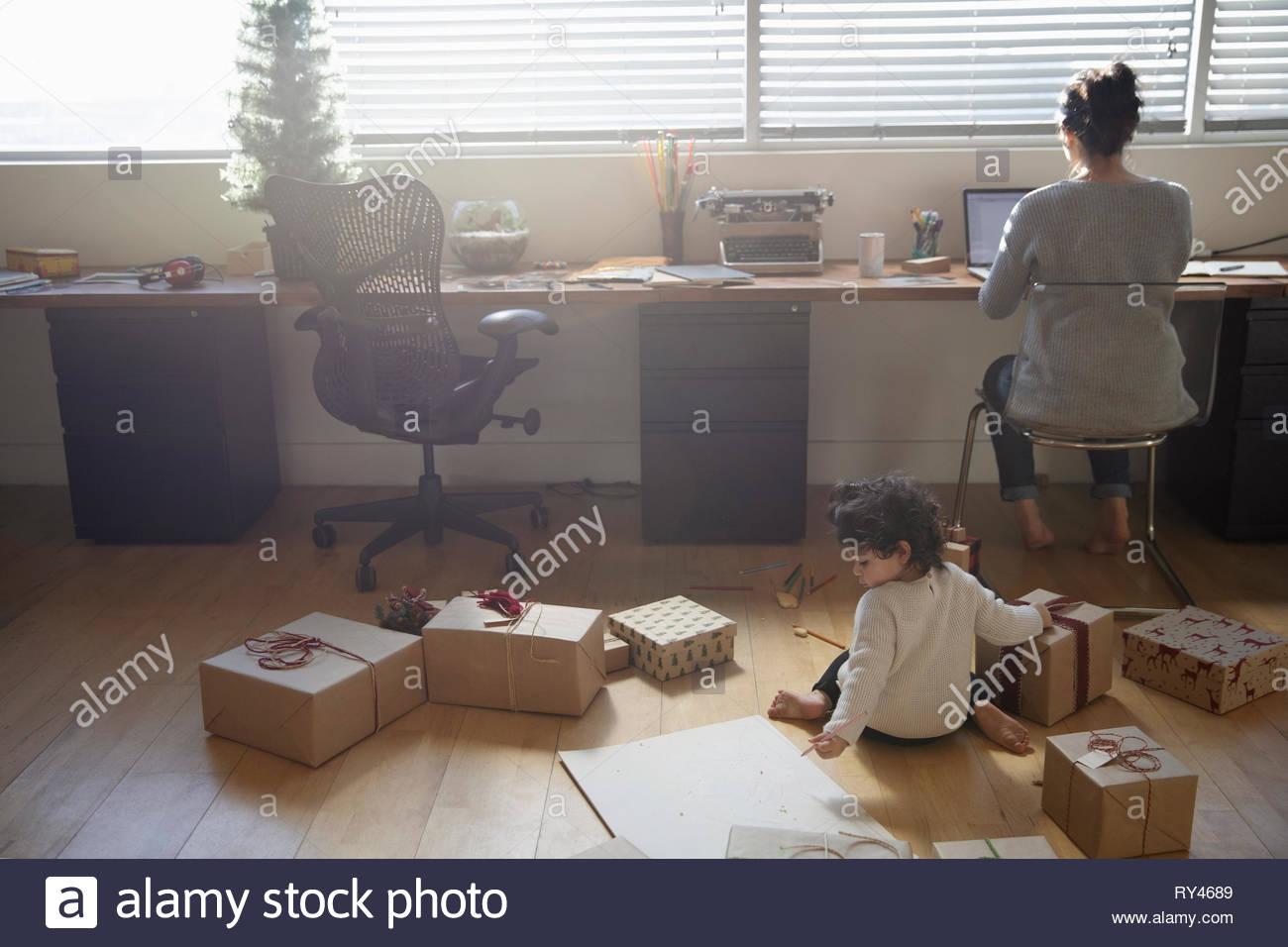Il Toddler girl giocando con i regali di Natale sul pianale dietro la madre lavora al computer portatile Immagini Stock