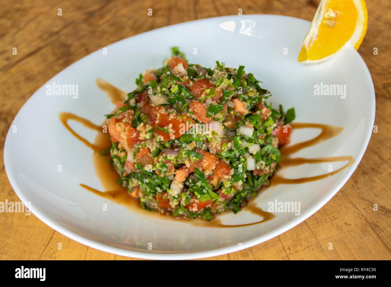 Tabule insalata. Con il prezzemolo, pomodori e cipolla rossa, manna groppa, il succo di melograno e spremuta di limone. Immagini Stock