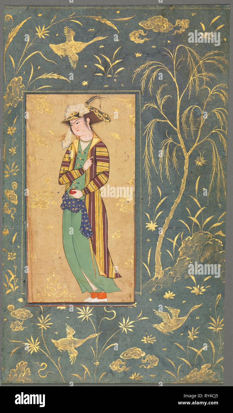 I giovani in possesso di una melagrana; illustrazione da una singola pagina manoscritta, c.1600-1650. Stile di Riza-yi Abbasi (iraniana). Acquerello opaco e oro su carta; immagine: 15,3 x 8 cm (6 x 3 1/8 in.), in totale: 27,7 x 16,4 cm (10 7/8 x 6 7/16 in Immagini Stock