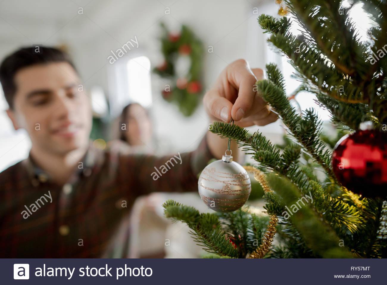 Giovane uomo appeso ornamento su albero di natale Immagini Stock