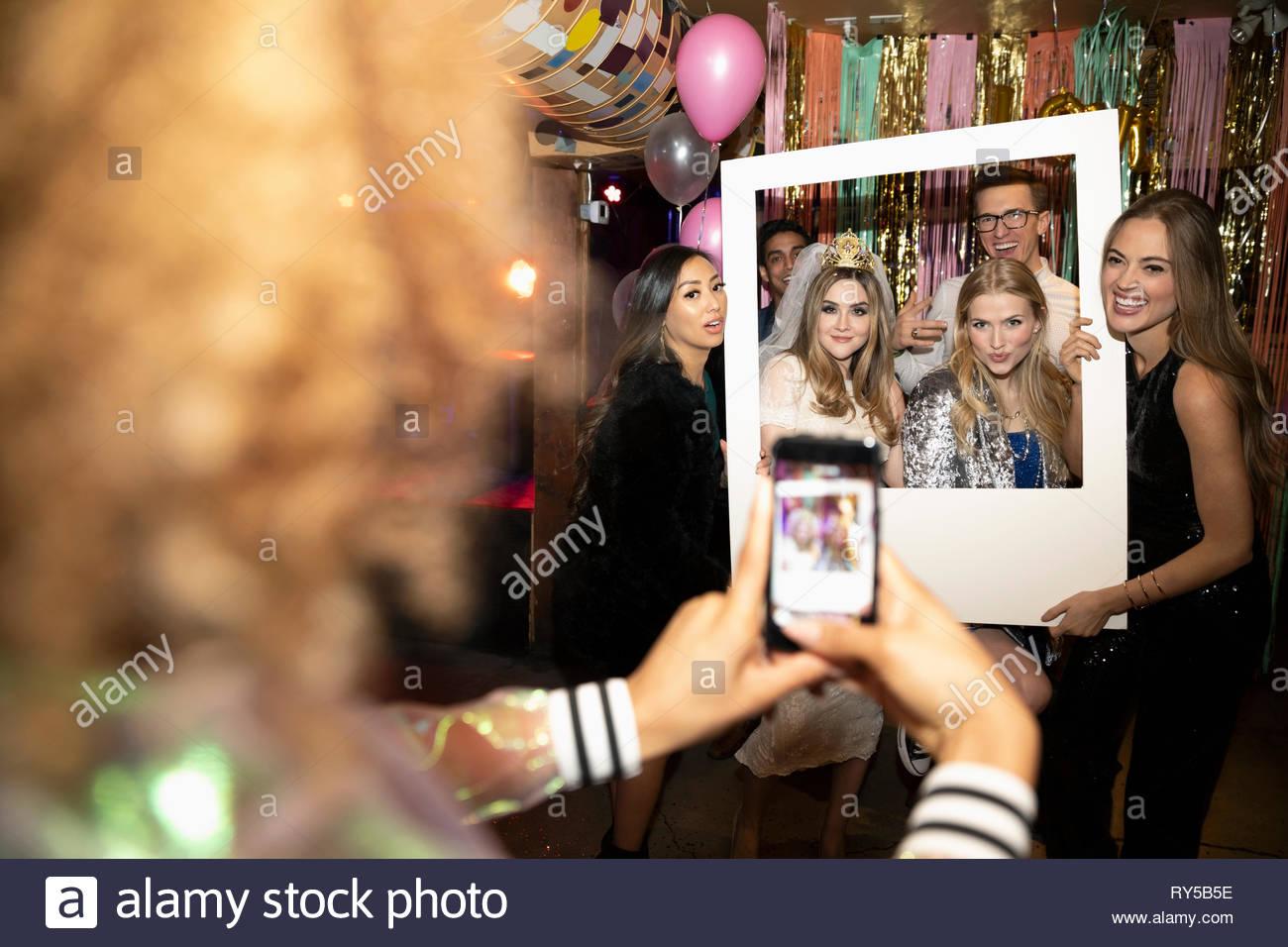 Donna con la fotocamera del telefono a fotografare gli amici creando per il Photo Booth a parte Immagini Stock