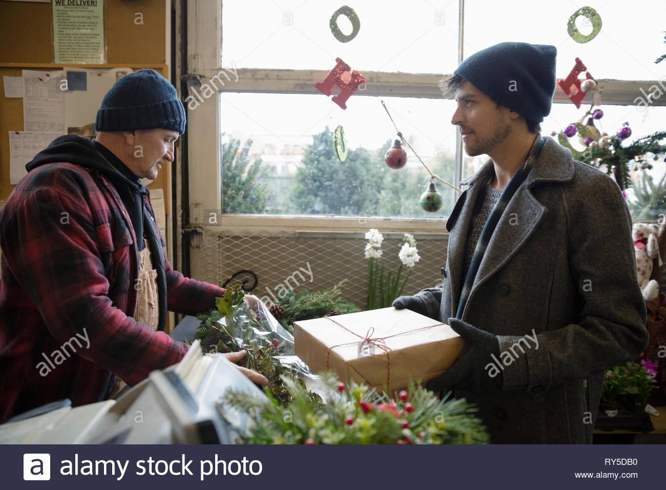 L'uomo acquistare decorazioni di Natale e il regalo al mercatino di natale Immagini Stock