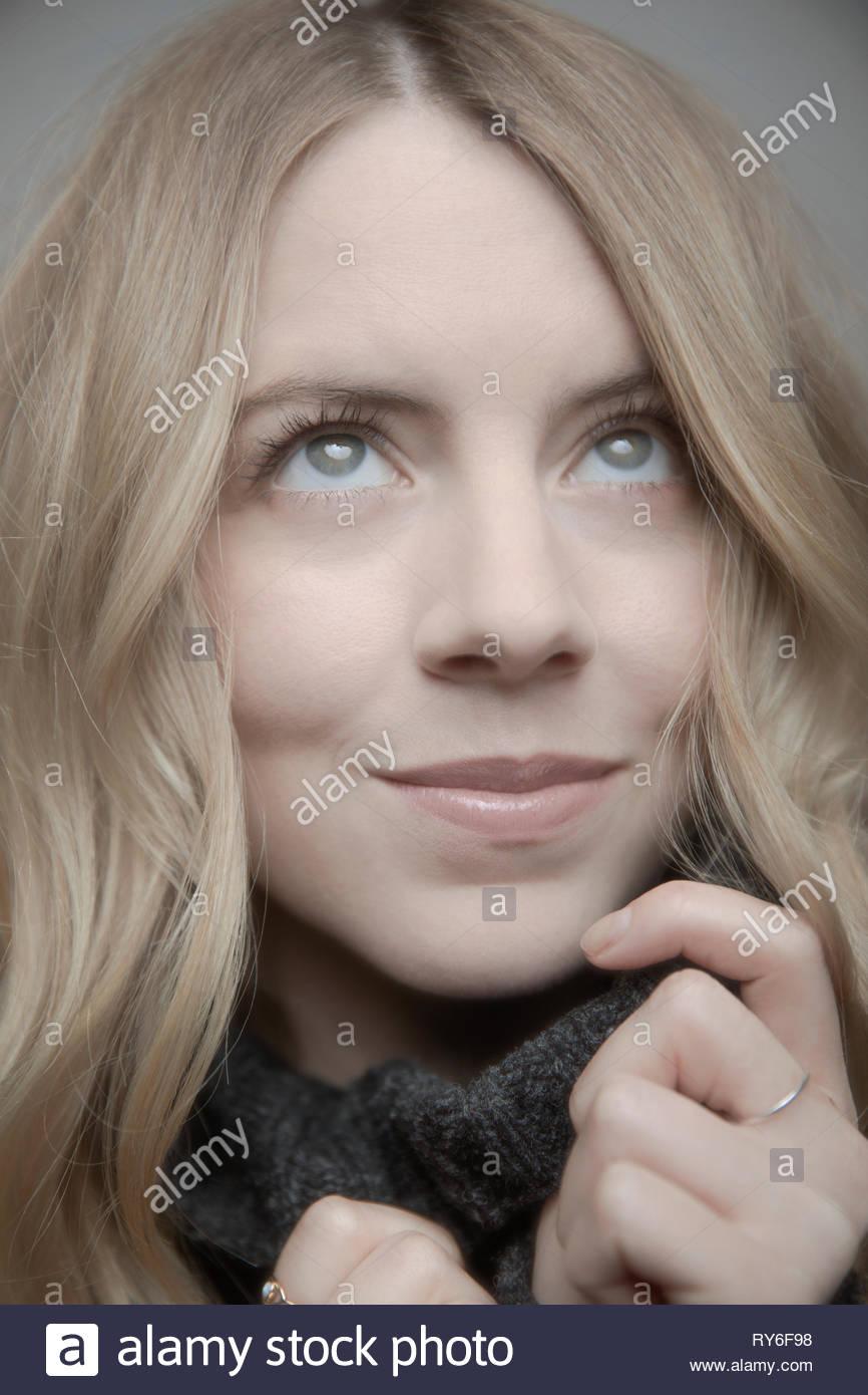 Close up ritratto giovane e bella donna con capelli biondi e occhi blu guardando in alto Immagini Stock