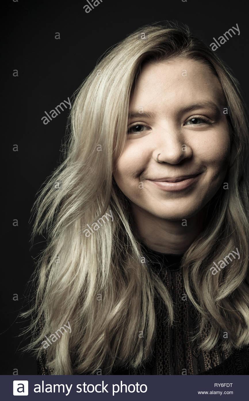 Ritratto fiducioso giovane e bella donna con capelli biondi e naso anello Immagini Stock