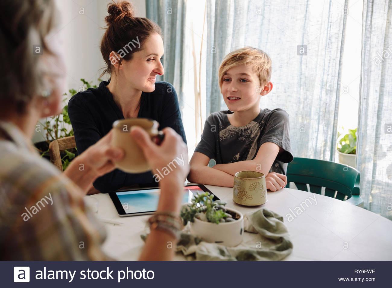 Multi-generazione parla di famiglia al tavolo della cucina Immagini Stock