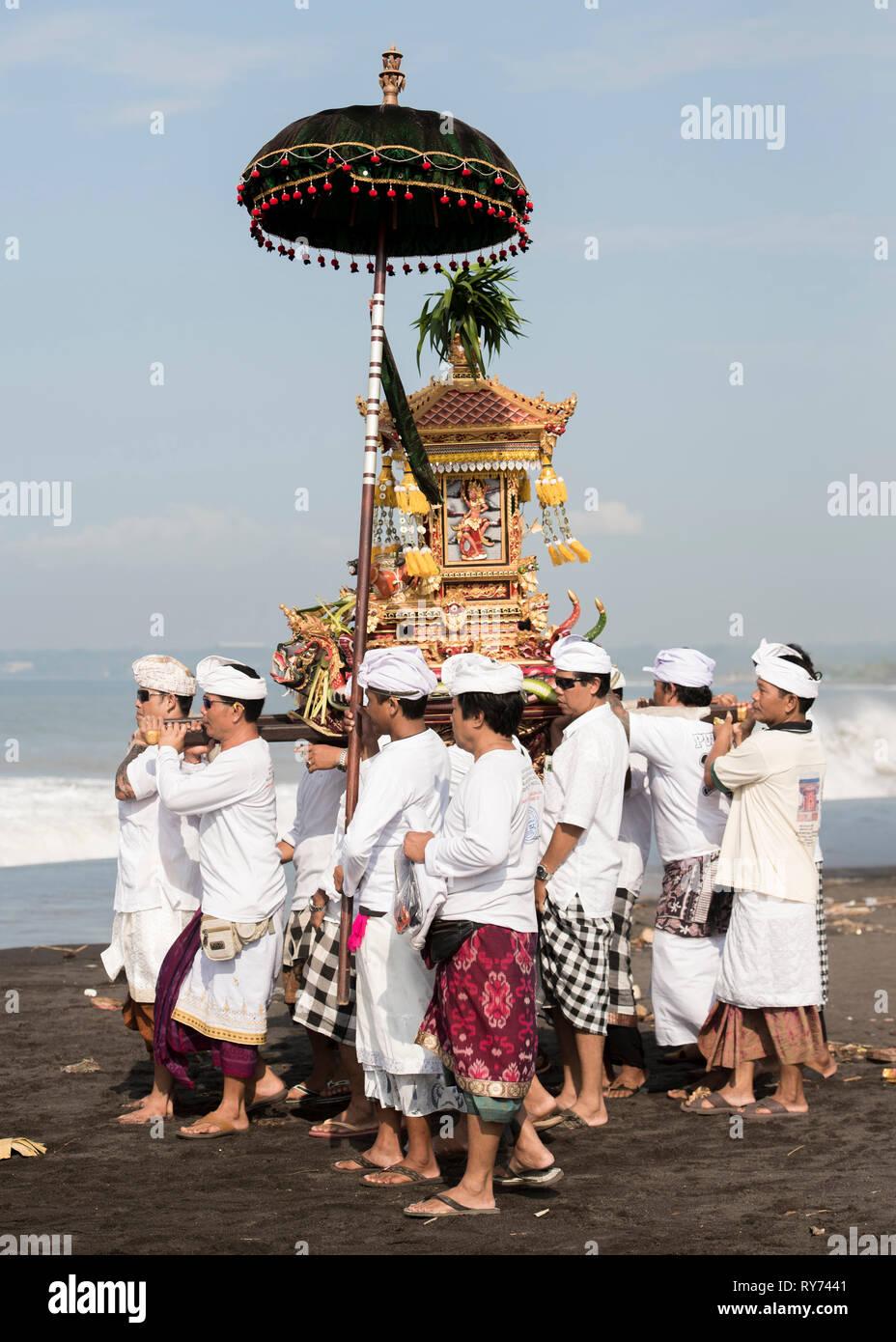 Gli uomini in abiti tradizionali che trasportano palanquin mentre passeggiate in spiaggia contro il cielo durante la giornata di sole Immagini Stock