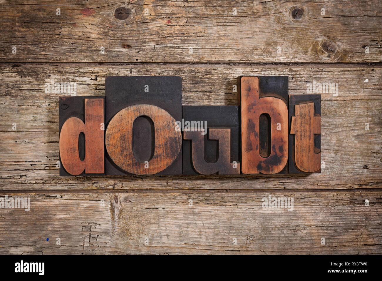 Dubbio, singola parola insieme con l'annata tipografia su blocchi di legno rustico sfondo Immagini Stock