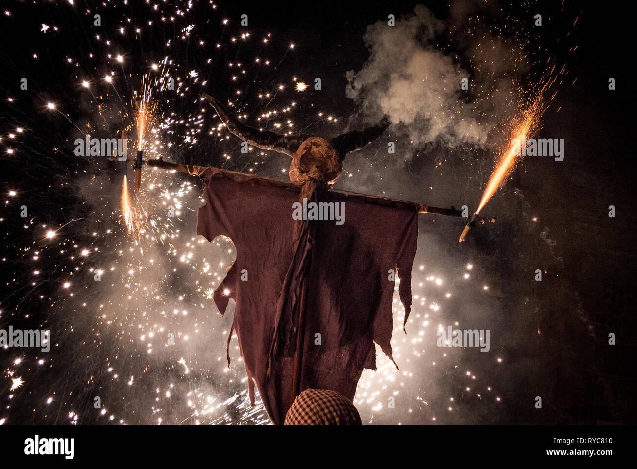 A due corna demone. Durante il Correfoc celebrazioni tradizionali, fuochi d'artificio-toting demoni rush selvaggiamente verso il basso le strade scattering scintille in un ardente ri-e Immagini Stock
