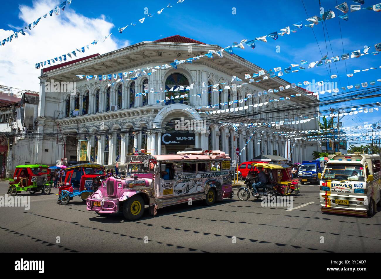 Rosa Jeepney e colorato triciclo il traffico a croce con edificio storico - Tacloban City, Leyte - Filippine Foto Stock