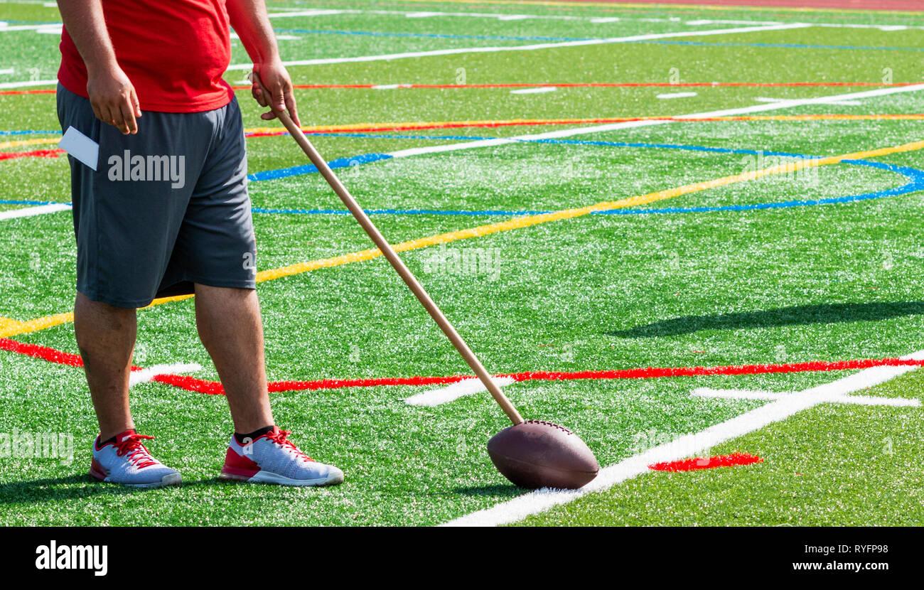 Un allenatore di calcio è su un tappeto erboso verde campo tenendo un calcio sul terreno che è attaccato a un memory stick durante l'estate pratica di preseason. Immagini Stock