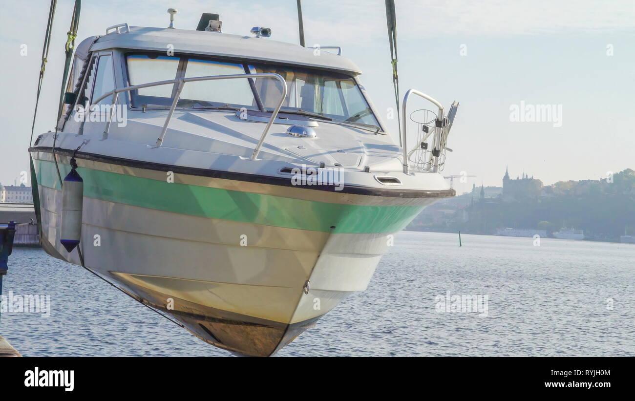 Uno sguardo più da vicino della bianca motoscafo sul porto di Stoccolma Svezia essendo sollevata da un camion gru Immagini Stock