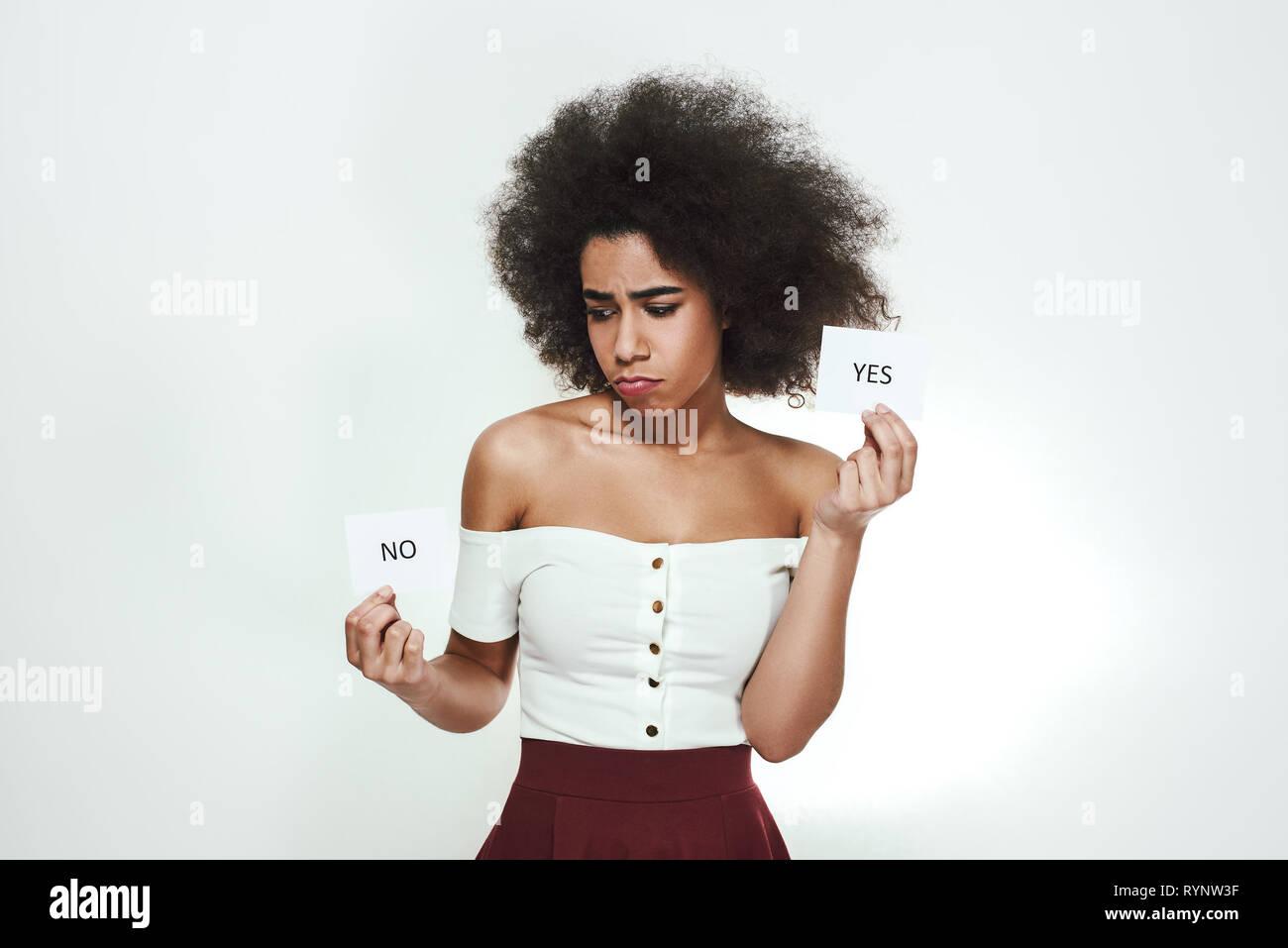 Io non sono sicuro...confuso giovani afro american donna è in possesso di carte con sì e no su di loro e pensare mentre in piedi contro uno sfondo grigio. Concetto di dubbio. Processo di pensiero Immagini Stock