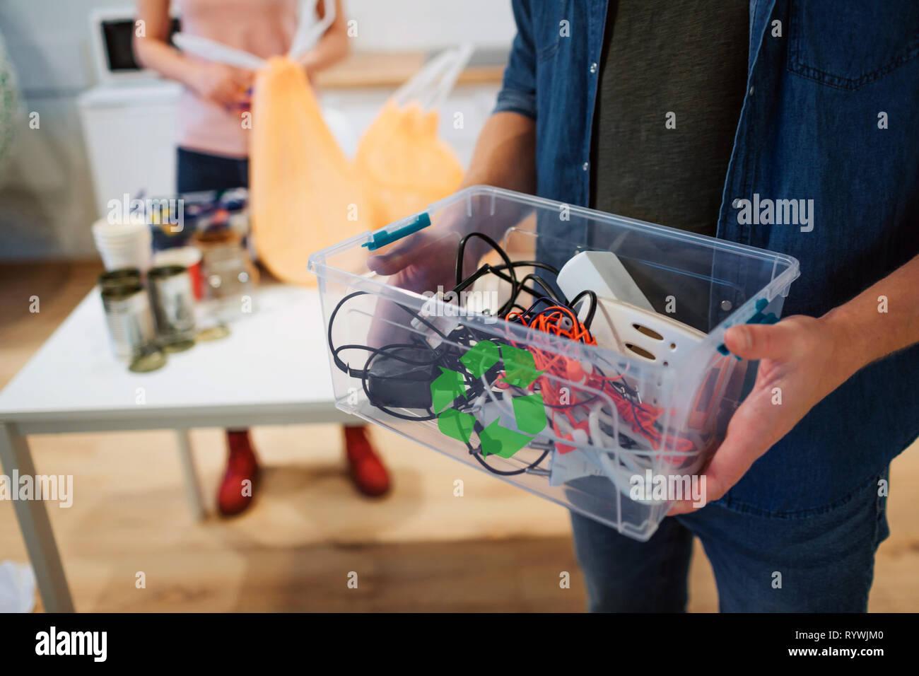 Il riciclaggio. Mescolati rifiuti elettronici in plastica contaner close-up. L'uomo responsabile è la protezione dell'ambiente, mentre la cernita dei rifiuti a casa Immagini Stock