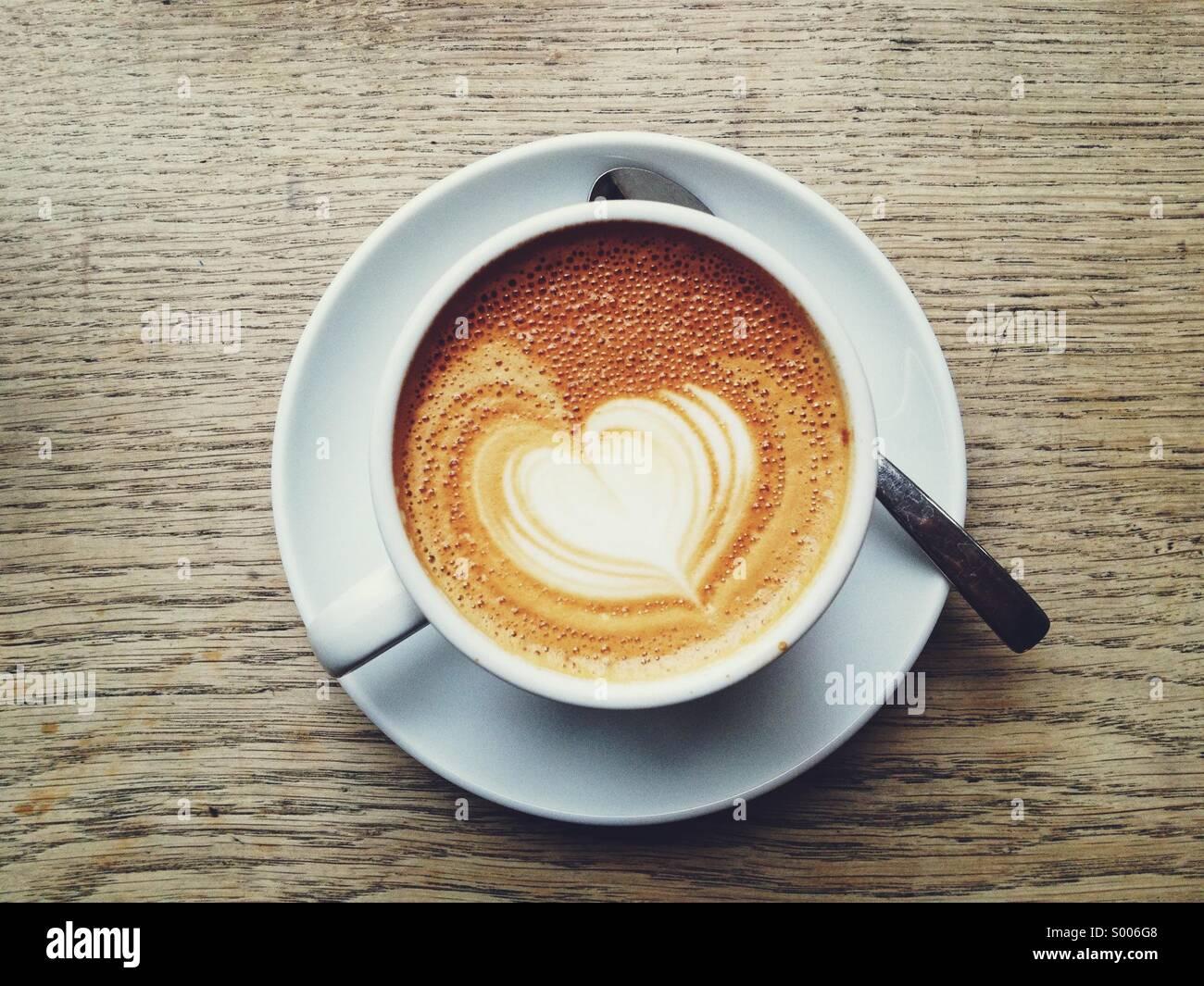 A forma di cuore ad arte del caffè su una tazza di latte Immagini Stock