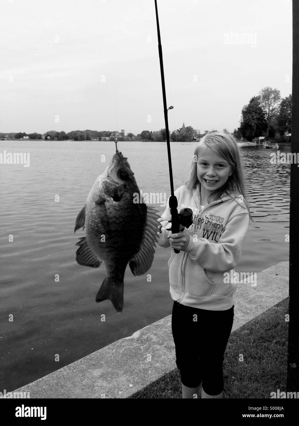 Una giovane ragazza sorride dopo la cattura di un pesce. Foto Stock