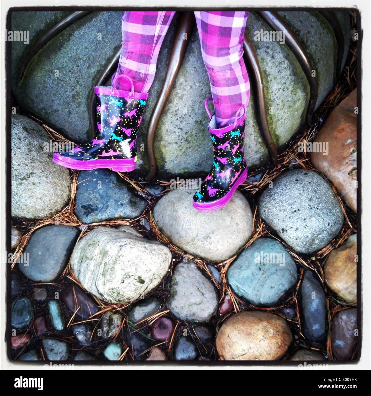 Le ragazze giovani gambe su roccia, indossare stivali da pioggia. Immagini Stock