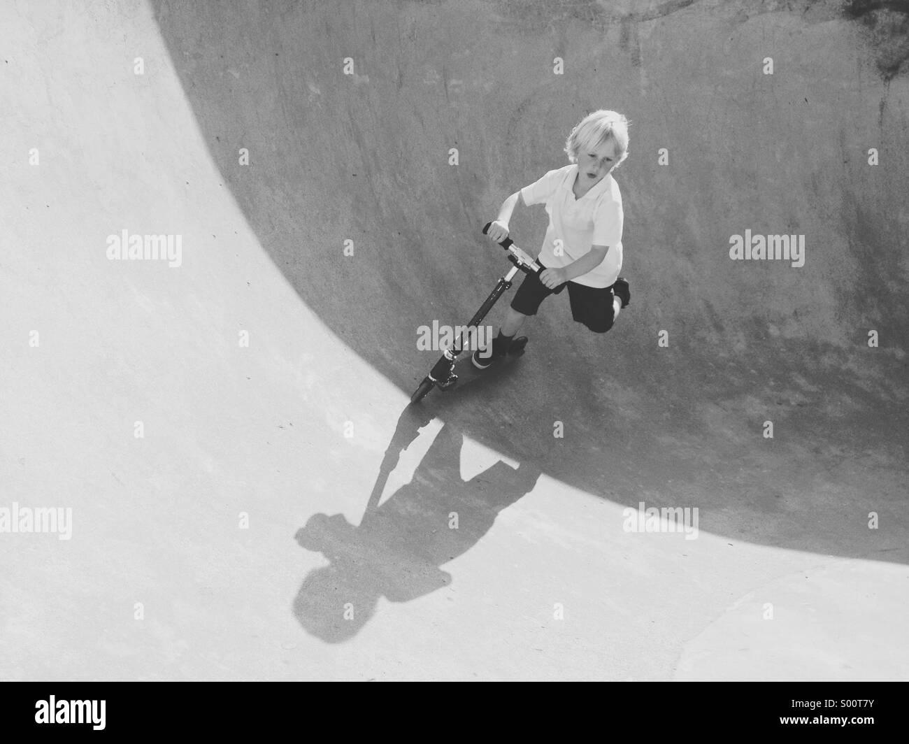 Giovane ragazzo in sella al suo scooter a skate park. Immagini Stock