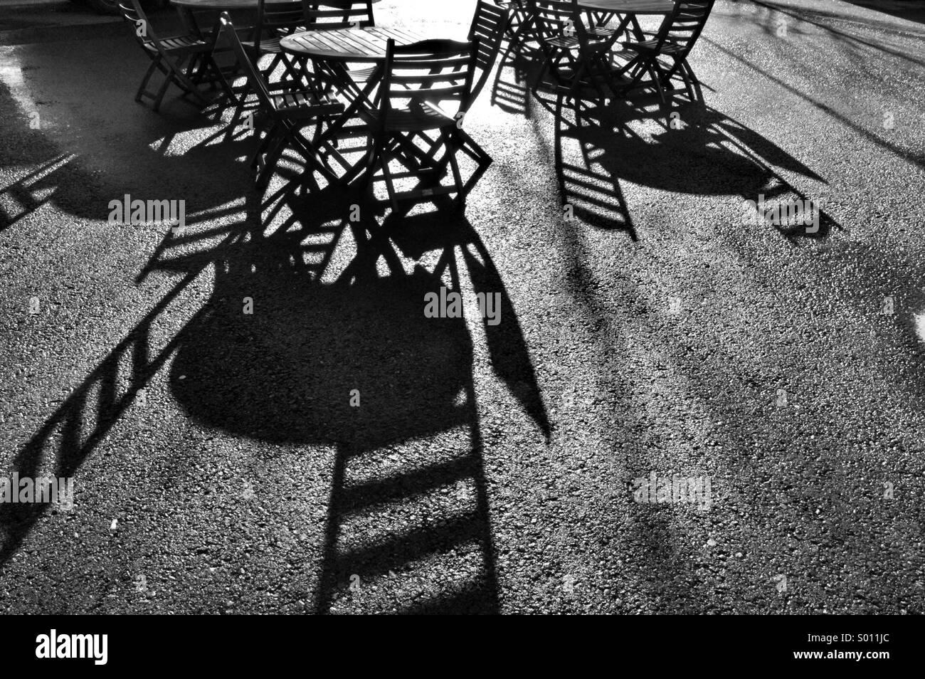 Silhouette di cafe tabelle nel sole del pomeriggio. Immagini Stock