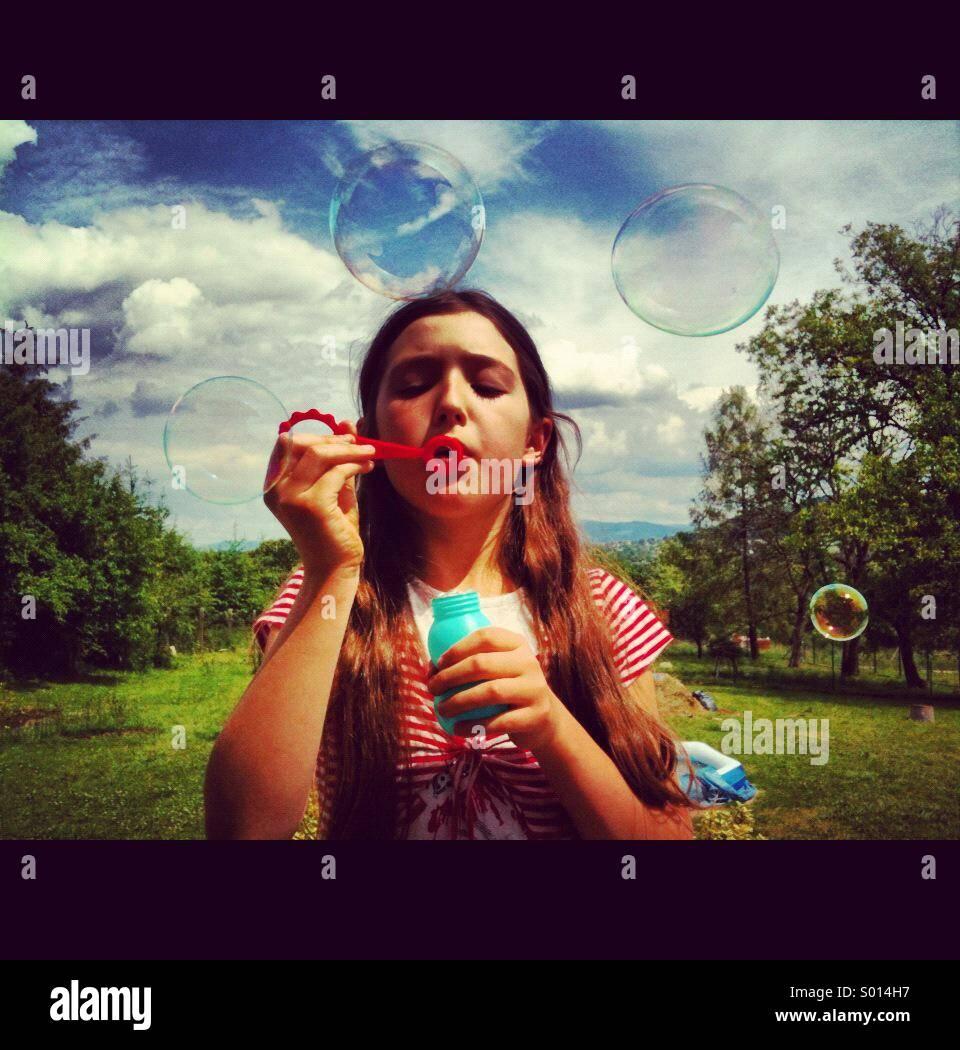 Ragazza giovane soffiare bolle su una giornata d'estate. Immagini Stock