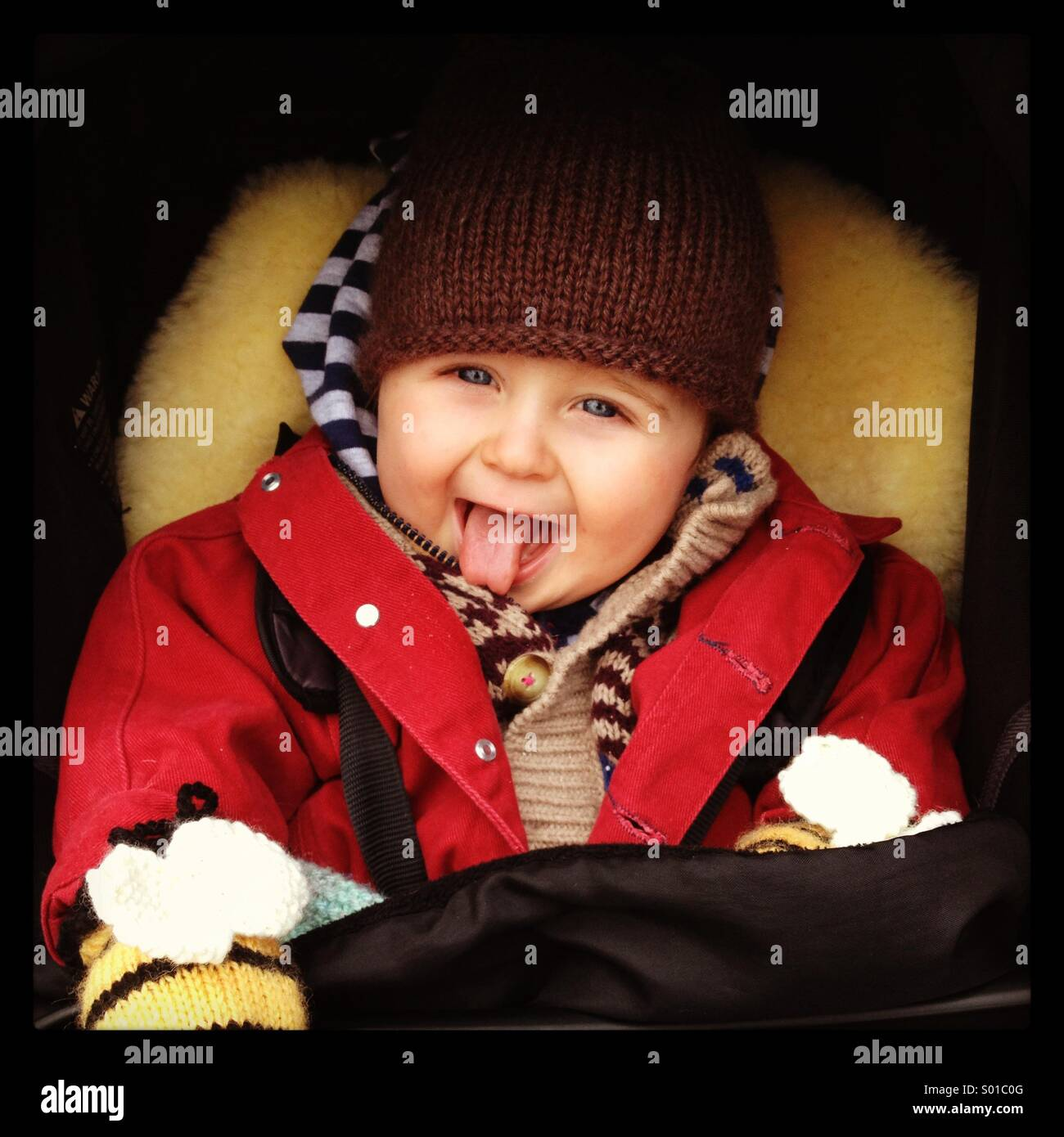 Baby prendendo la sua con la lingua fuori Immagini Stock