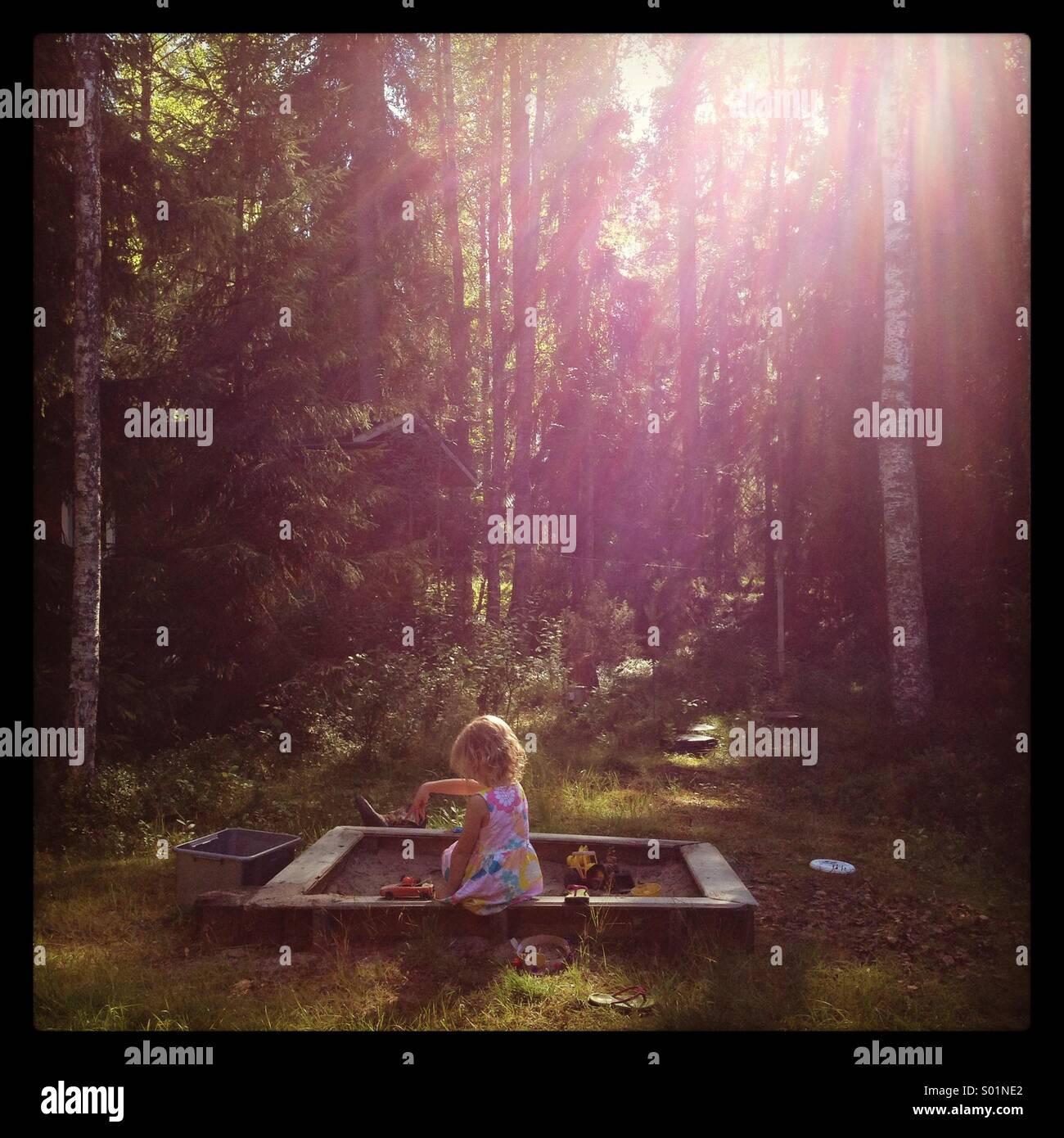 Una giovane ragazza che gioca in una sandbox in un sogno sole inzuppato forest Immagini Stock