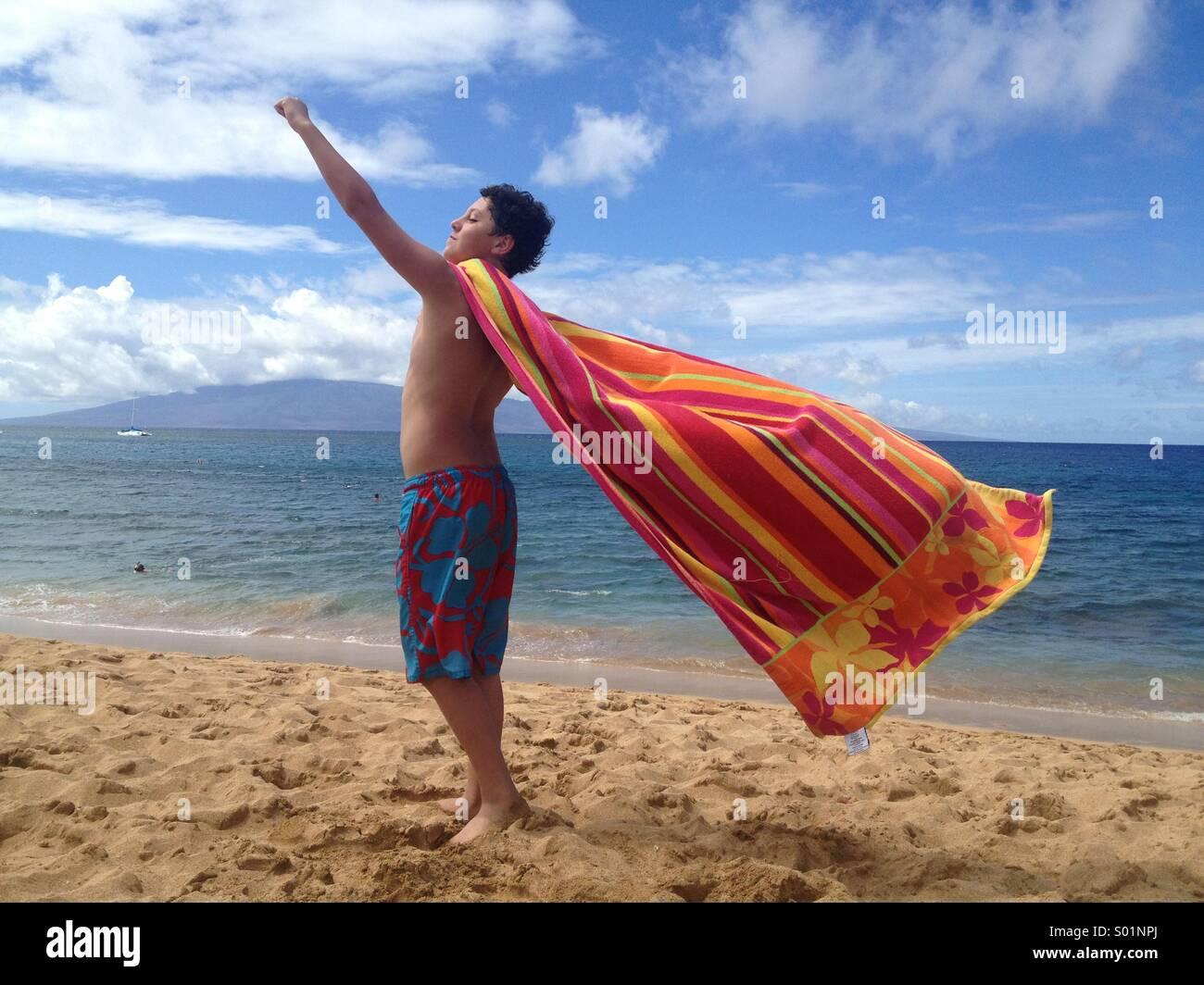 Il ragazzo, di età compresa tra i 12, giocando con il telo da spiaggia, Hawaii Immagini Stock