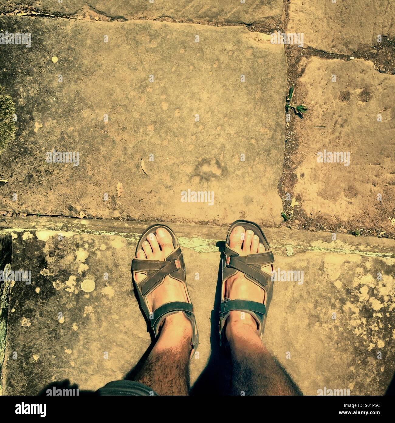 I miei due piedi sandalled esplorando un tempio in rovina della Cambogia re Khmer Immagini Stock