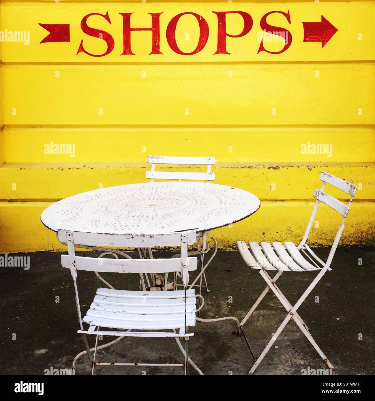 Segno per i negozi sulla parete gialla con il bianco giardino con sedie e tavolo Immagini Stock