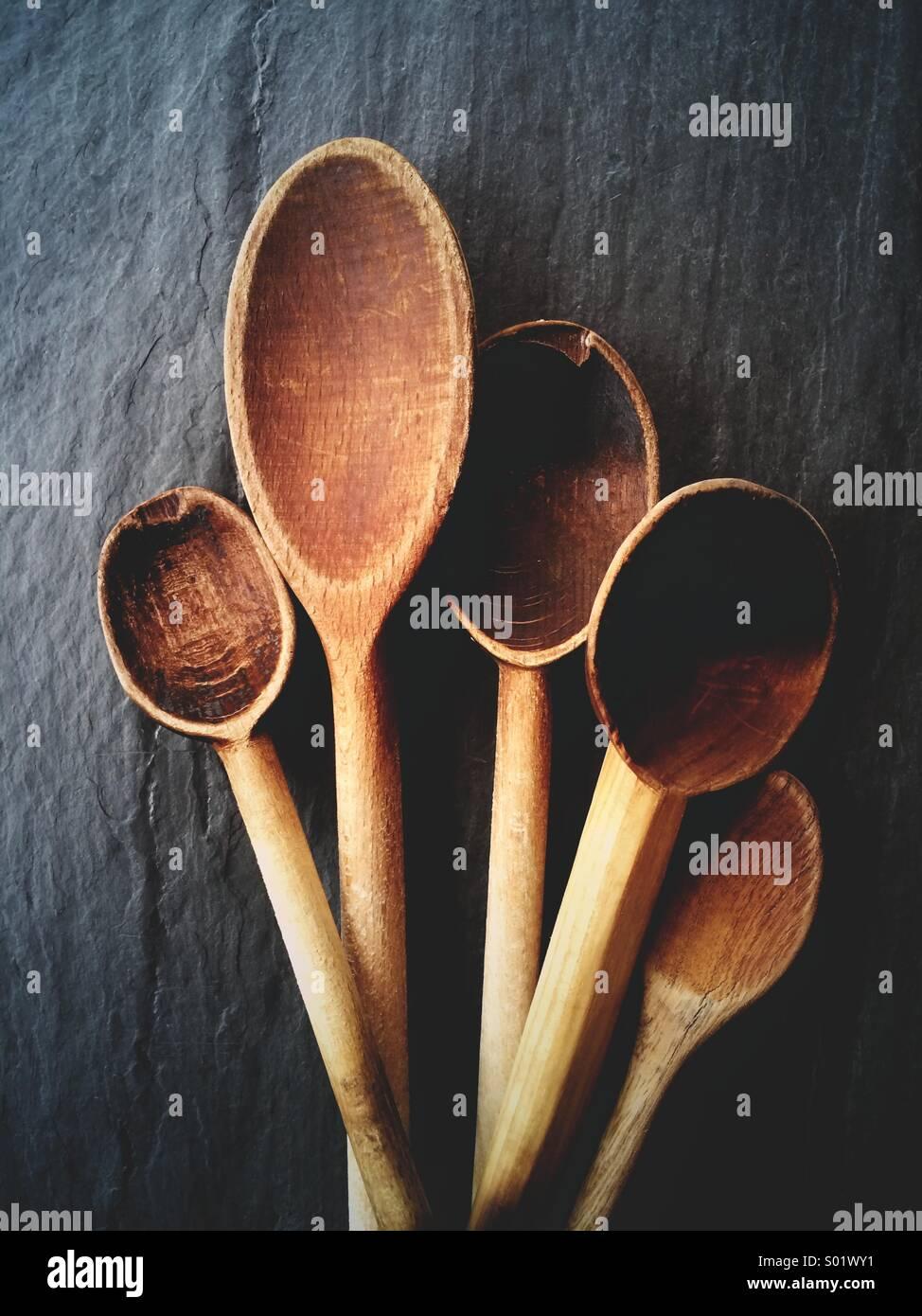 Bella e antica cucchiai di legno per la cottura su un sfondo di ardesia. Immagini Stock