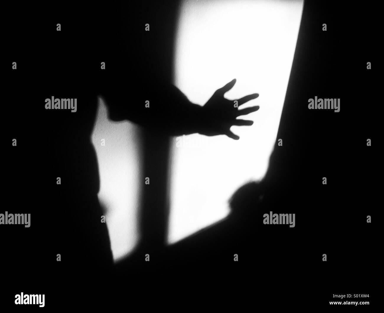 Ombra di mano contro la parete Immagini Stock