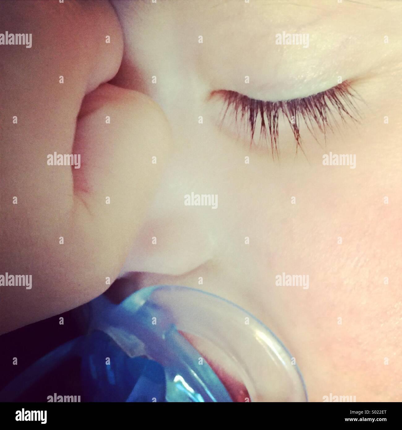 Close-up di un bambino che dorme con un manichino blu succhietto nella sua bocca. Foto Stock