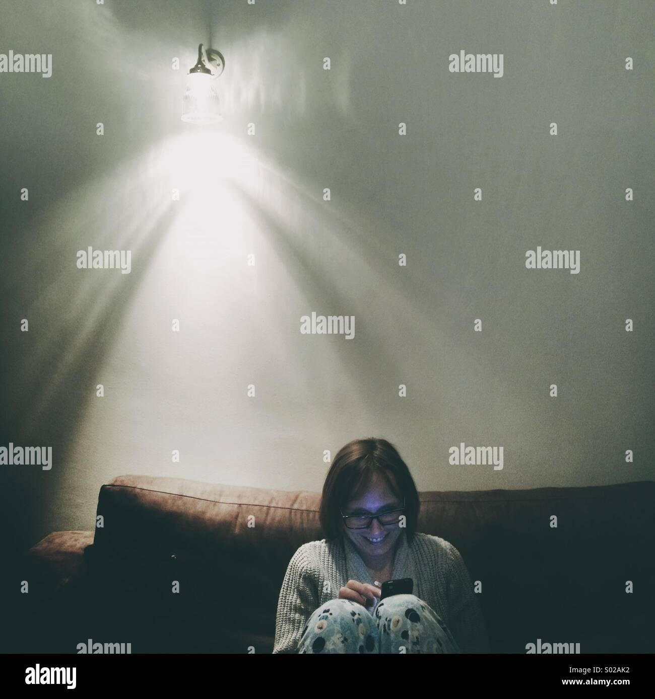 Signora a casa sul divano sotto una luce da parete in chat tramite social media su un telefono cellulare Immagini Stock