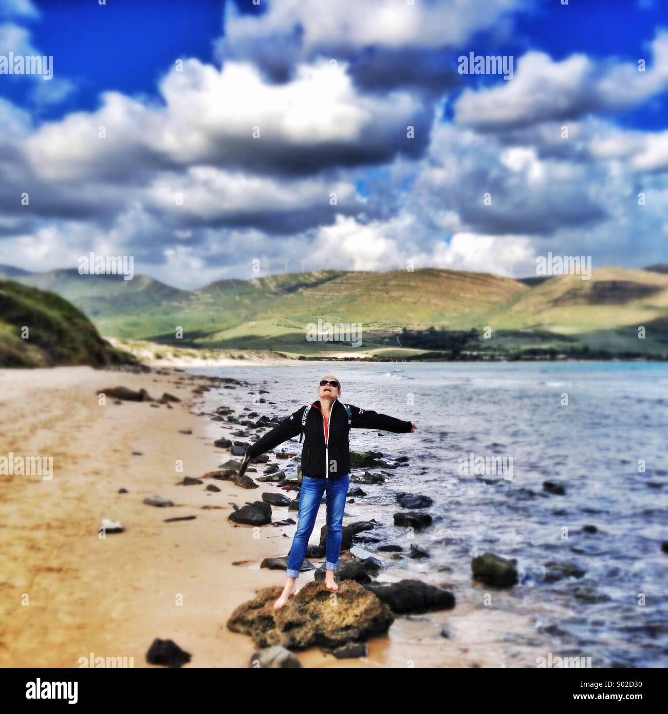 All'esterno la ragazza in piedi sulla roccia alla spiaggia Immagini Stock